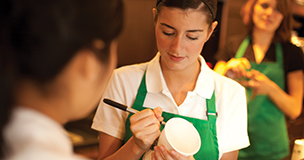 Barista Writing Customer's Name On The Coffee Cup